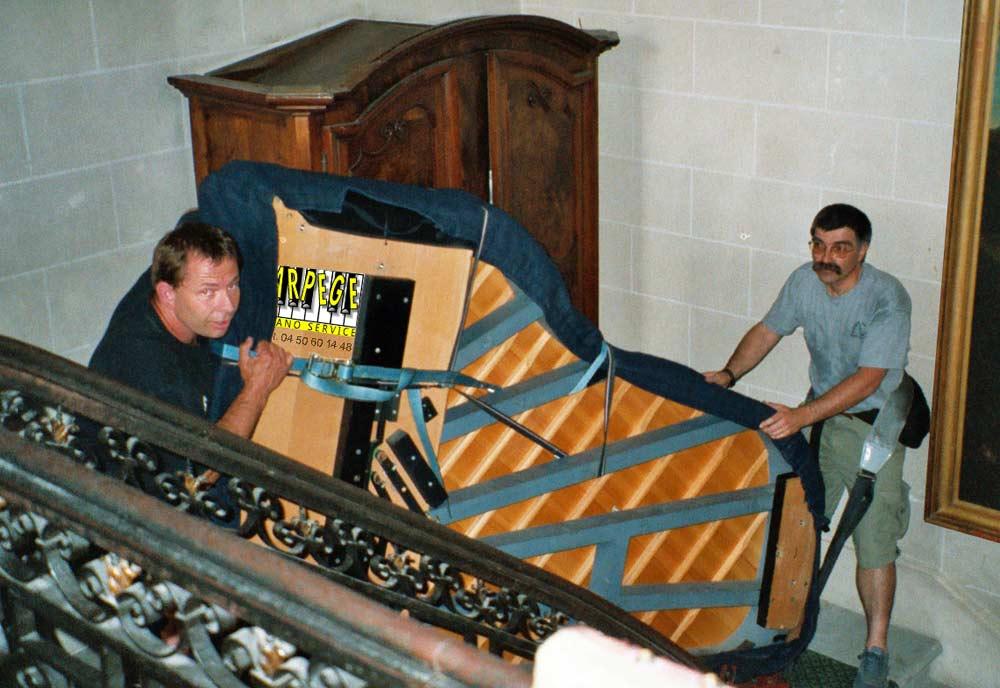 Transport, port d'un piano à queue dans cage d'escaliers d'apparat par 2 porteurs et des sangles de portage