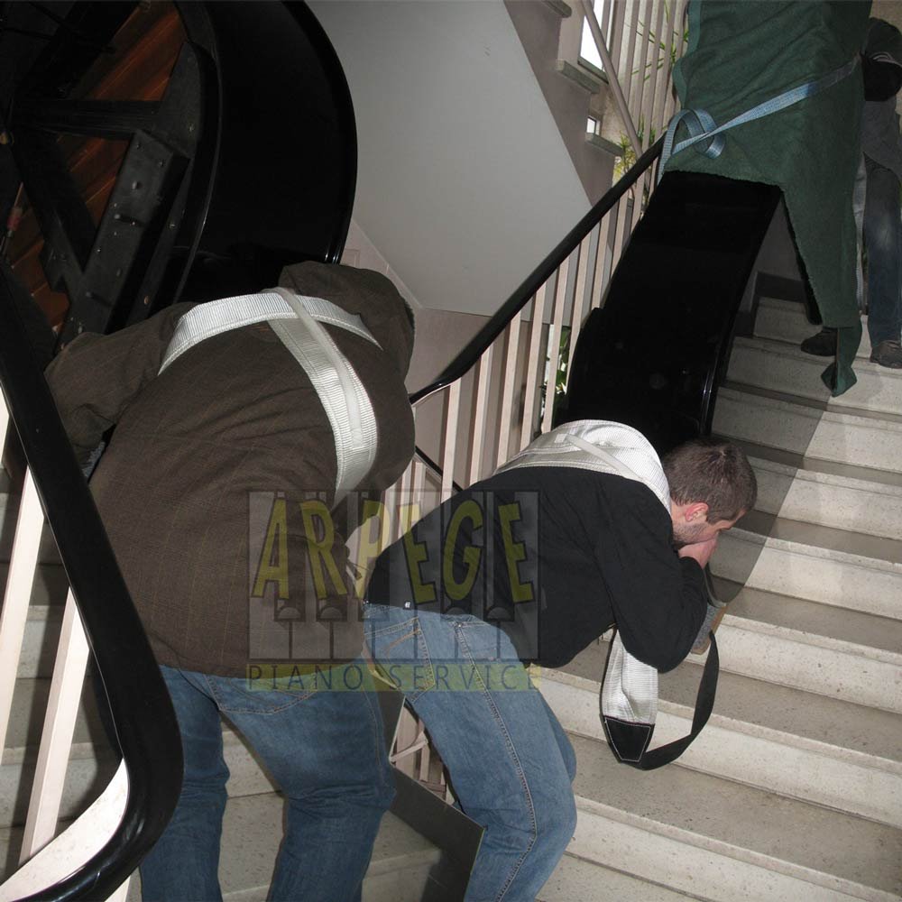 Transport, port d'un piano à queue dans cage d'escaliers par 2 porteurs et des sangles de portage